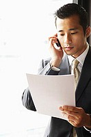 Businessman looking at document, using mobile phone