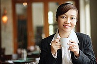 Businesswoman in restaurant, holding cup, looking at camera