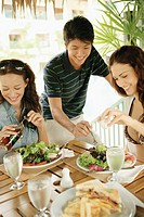 A group of friends having a meal, man helping himself to salad