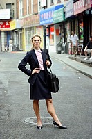 Business woman standing in the middle of chinatown street looking in the camera