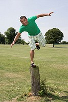Man balancing on tree stump