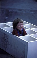 Child with a bib overall siting in a wodden box