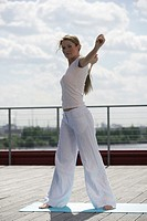 A blonde woman exercising with a skipping rope.