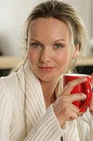 A blonde woman having a cup of coffee