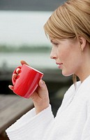 Woman lost in her thoughts as drinks a cup of coffee.