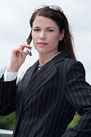 A woman looks at the camera as she holds the cell phone.