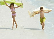 Two children running on beach, holding up towels in wind