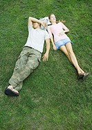 Young couple lying in grass with heads resting on books, high angle view