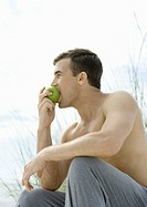 Barechested man eating apple, side view