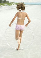 Girl running with plastic hoop on beach