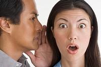Man Whispering to Shocked Woman