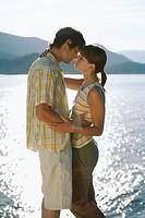 Couple kissing beside a lake