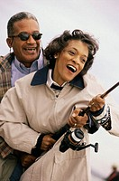 Close-up of a mature couple holding a fishing rod