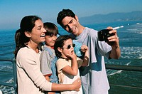 Mid adult man taking a photograph of his family