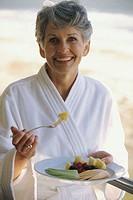 Portrait of a mature woman eating fruit salad
