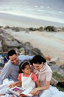 Young couple and their daughter reading a book on the beach