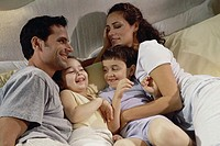 High angle view of parents and their two children lying in bed