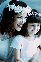Close-up of a bride with a flower girl laughing