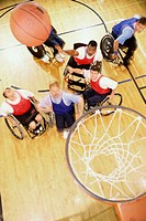 High angle view of a group of mid adult men in wheelchairs playing basketball