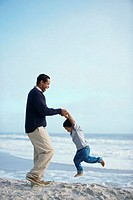 Side profile of a father swinging his son on the beach