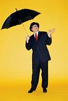 Portrait of a businessman holding an umbrella