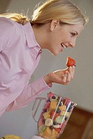 Side profile of a young woman eating a strawberry