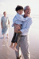 Grandfather carrying his grandson on the beach