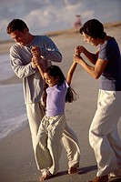 Parents swinging their daughter on the beach