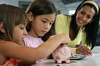 Mother looking at her two daughters inserting coins into a piggy bank