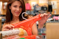 Young woman holding underwear in a clothing store