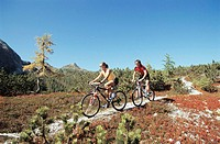 Couple riding bicycle in mountains
