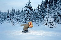 Young man carrying Christmas gift in snow, side view
