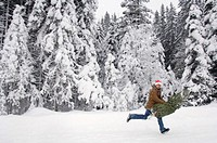 Man running in snow, carrying christmas tree