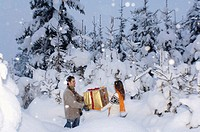 Young couple holding gift in snow, side view
