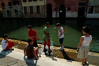 Group of boys at the side of a canal, Venice, Veneto, Italy