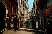 Three people standing on a footbridge over a canal, Venice, Veneto, Italy
