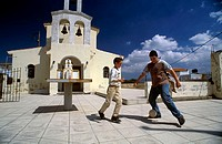 Two boys playing soccer in the courtyard of a church, Crete, Greece
