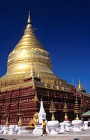 Burma (Myanmar), Bagan, Shwezigon Paya, golden temple, local woman walks in front.