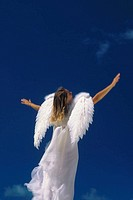Woman in angel costume, white dress and wings, view from behind, standing in front of blue sky
