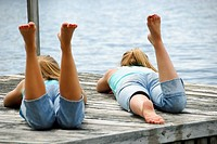 sisters 13 and 18 yrs laying on dock