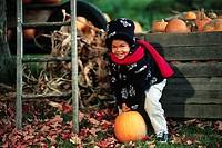 Child Lifting a Pumpkin