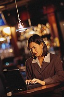 Businesswoman Typing on Laptop at a Bar