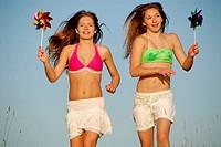 girl 13, girl 18 yrs running with pinwheels at the beach