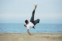 Caucasian male practicing soccer on beach
