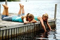 girl 13, girl 18 laying on dock together