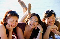 3 asian women laying together on beach
