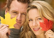 Couple Holding Fall Colored Leaves