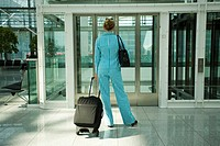 Airport hall, woman, pant suit,  Trolley, stand, waiting, view from behind,   Series, 30-40 years, businesswoman, wait, alone,  Lifestyle, concept, tr...