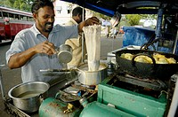Indian street cook preparing tea and streetfood (pakora, fritters) in his small mobile cook-shop. Fort Cochin (Kochi), Kerala, India 2005.