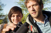 Young couple in mountains, man holding binocular